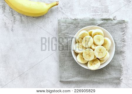 Sliced Ripe Banana In Bowl On Stone Background With Copy Space. Healthy Natural Food. Top View, Flat