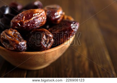 Dried Dates Friuts In Old Wooden Bowl On Wooden Background