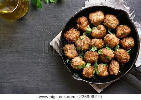 Meatballs In Frying Pan On Black Stone Background With Copy Space. Top View, Flat Lay