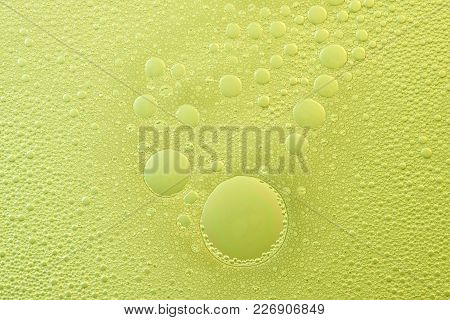 Foam Bubbles On Yellow Liquid Abstract Background. Foam Texture