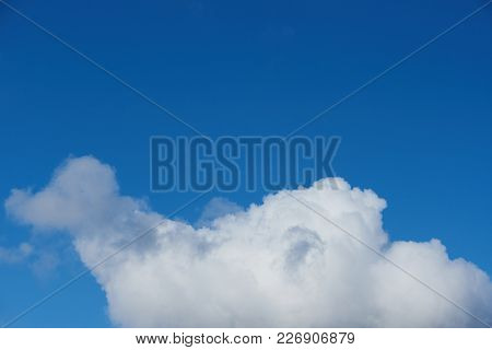White Cloud With Copyspace On Blue Sky Background. One Big Gray Cloud