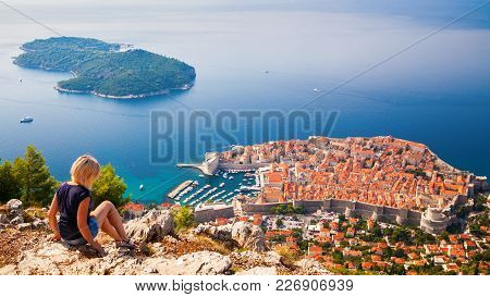 Unrecognizable Woman Looking At The Dubrovnik Old Town, Sitting On The Mountain Above The City, Croa