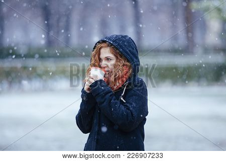 Woman Drinking A Hot Beverage Under The Snow In The Park