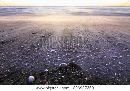 Long Exposure Of Waves Flowing Over Rocks At Sunset On Hokitika Beach On The West Coast Of New Zeala