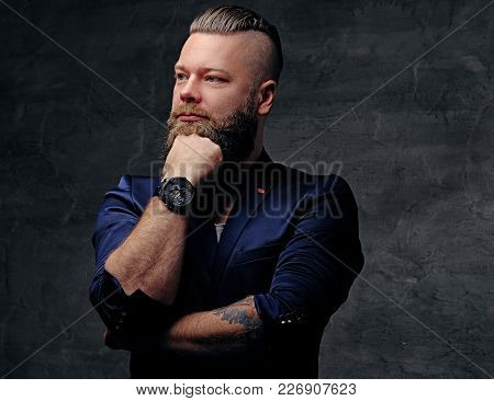 Thoughtful Bearded Punk Man In A Purple Jacket, Isolated On Grey Background.