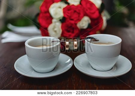 Wedding Bouquet And Coffee With The Wedding Rings On The Table