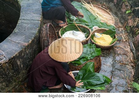 Vietnamese Woman Preparing To Make Chung Cake, The Vietnamese Lunar New Year Tet Food Outdoor By Old