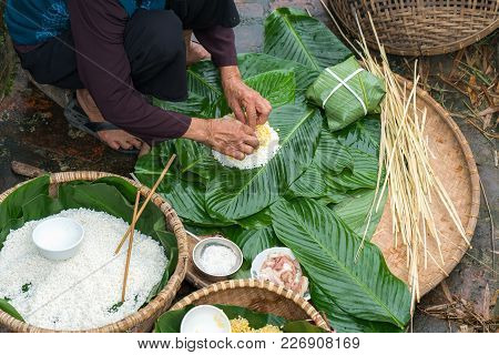Making (wrapping) Chung Cake, The Vietnamese Lunar New Year Tet Food Outdoor With Old Woman Hands An
