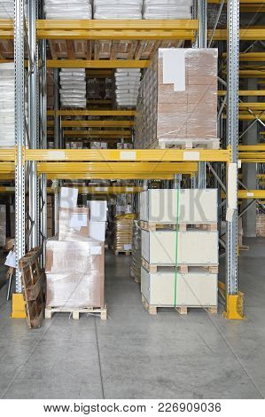 Pallets And Boxes At Shelves In Distribution Warehouse