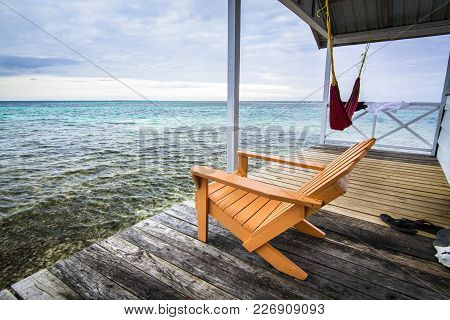 An Armchair Sits On A Deck Overlooking The Caribbean Sea. Photographed On Tobacco Caye, Belize.