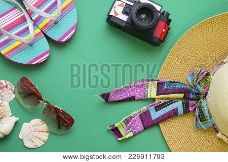 Woman Prepares For A Seaside Trip. Green One-color Background With A Roll Film Camera, A Straw Hat,