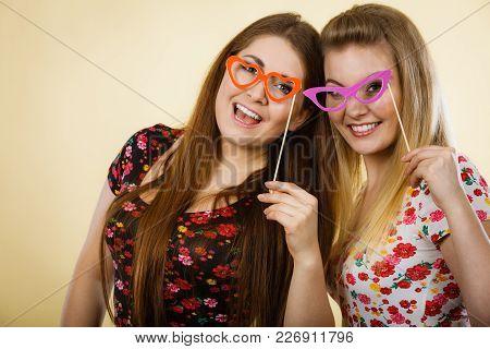 Two Happy Women Holding Fake Eyeglasses On Stick Having Fun Wearing Tshirts With Flower Pattern. Pho