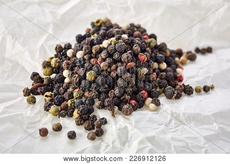Black, Red And White Peppercorns Isolated On White Textured Background. Heap Of Spice. Mix Of Differ