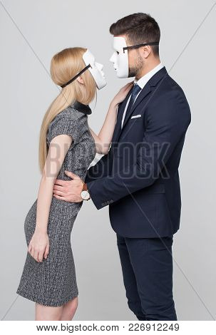 Young Man And Woman In Formal Wear And Mask Flirting
