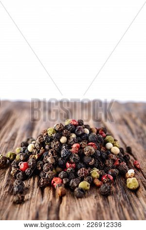 Black, Red And White Peppercorns Isolated On Dark Wooden Background. Heap Of Spice. Mix Of Different