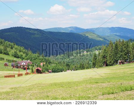 Countryside Landscapes Of Grassy Field And Forest At Beskid Mountains Range On Bialy Krzyz In Poland