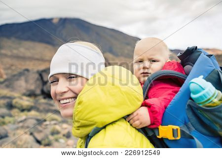 Happy Mother With Little Boy Travelling In Backpack