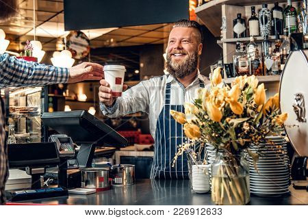 Positive Bearded Barista Male Selling Coffee To A Consumer In A Coffee Shop.