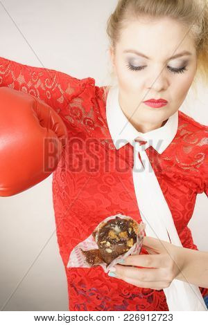 Dieting, Weight Loss Concept. Funny Blonde Woman Holding Yummy Chocolate Cupcake Cake And Boxing Glo