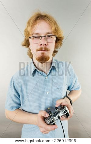 Nerd Geek Young Adult Man Playing On The Video Console Holding Game Pad. Gaming Gamers Concept.