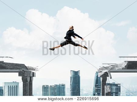 Business Woman Jumping Over Gap In Concrete Bridge As Symbol Of Overcoming Challenges. Cityscape On