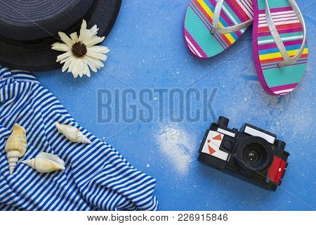 Get Ready To Travel. Tourist Concept. Blue Powdered Background With Slippers, Vintage Camera And Gre