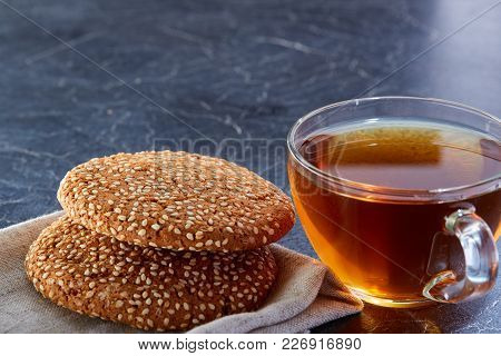 A Transparent Glass Cup Of Black Tea With Cookies On The Light Grey Cotton Napkin On A Dark Greyish
