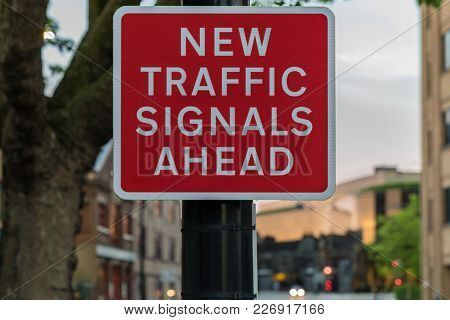 Sign: New Traffic Signals Ahead, With Some Blurry Traffic Signals In The Background, Seen In Ipswich