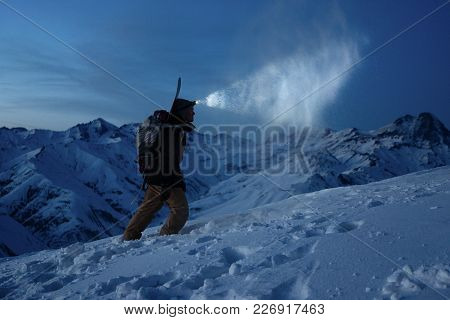 Ski Touring Man Commit Climb On Night Winter Mountain. Tourist With Headlamp, Backpack And A Snowboa
