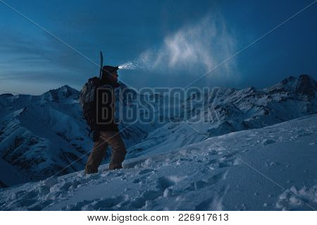Brave Man With Headlamp, Backpack And A Snowboard Behind His Back Climb Night On Snowy Mountain. Man