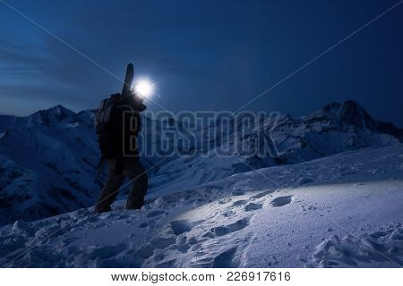 Professional Tourist Commit Climb On Great Snowy Mountain At Night. Wearing Backpack, Headlamp And S