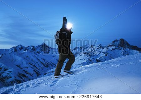 Brave Explorer With Headlamp And Backpack And A Snowboard Behind His Back Climb On Great Snowy Mount