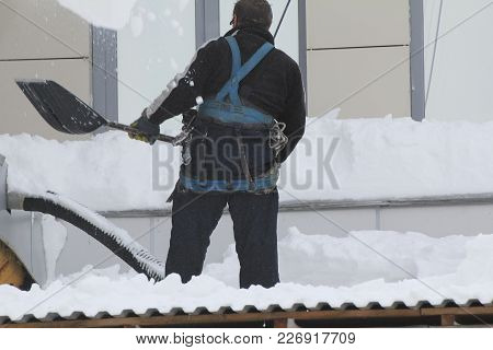 Worker Removing Snow From A Roof With A Snow Shovel, Urban Landscape