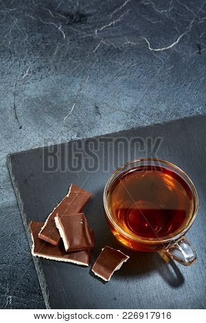 A Transparent Glass Cup Of Black Tea With Chocolate Pieces On A Dark Greyish Marble Background. Brea
