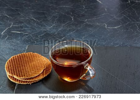 A Transparent Glass Cup Of Black Tea With Waffles On A Dark Greyish Marble Background. Breakfast Bac