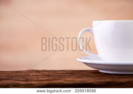 Side Close Up View Of Half A Tea Cup And Saucer On Dark Brown Wooden Vintage Table Background, Indoo