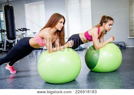 Fitness, Sport, Training And Lifestyle Concept - Two Young Woman Doing Physical Exercise With A Larg