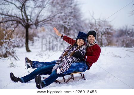 Lovely Couple Enjoy A Sleigh Ride. Lovely Couple Sledding. Funny Couple Play Outdoors In Snow. Happy