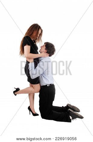 A Young Couple Loving Each Other, He Is Kneeling For Her And Hugging Her, Looking At Each Other, Iso