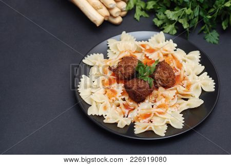 Farfalle Pasta With Meatballs And Sauce On Black Plate. Healthy Food.