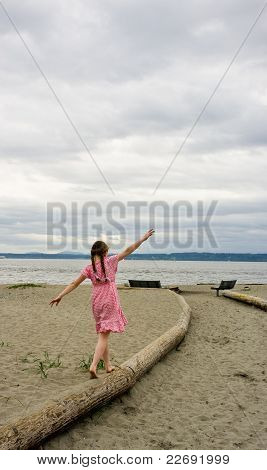 Young girl balancing on log at beach