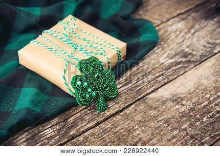Stylish Gift Box With Green Rope And Clover Brooch, On The Wooden Rustic Background.
