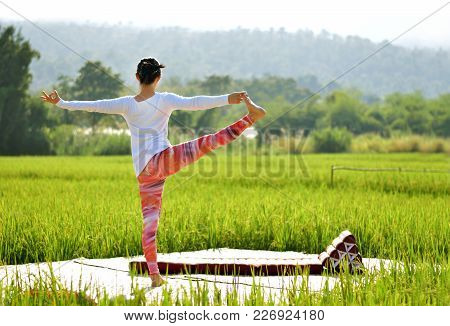 Soft Focus Image Of Woman Do Variation Of Utthita Hasta Padangusthasana Yoga Pose On Terrace In Gree