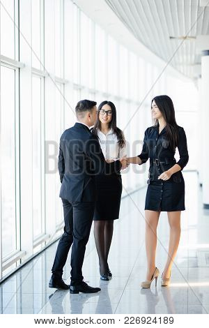 Full Body Businessman And Businesswoman Shaking Hands In Office Hall At Informal Meeting