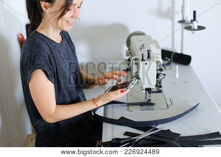 Seamstress Sewing Belt Using Sewing Machine. Girl Working At Factory, Female With Red Nails And Brac