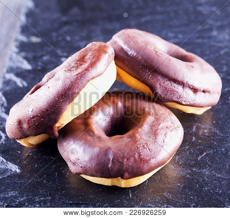 Chocolate Donuts Over Black Stone Background