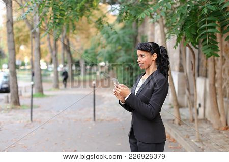 Fiancee Talking With Truelove On Smartphone In Park With Close Up Of Beautiful Face. Young Girl Has