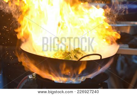 Burning Flame Over The Pan When Chef Cooking A Stir Fried Swamp Cabbage/water Spinach