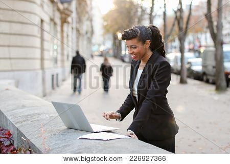 Young  Businesswoman Working With Laptop Near High Building On Balcony. Young Female Person Working