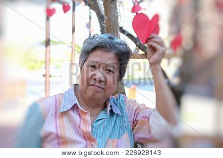Elder Woman Holding Red Heart Paper & Smiling At Camera. Happy Elderly Female Relaxing Outdoors. Mat